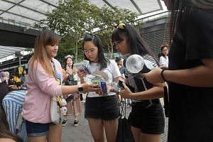 Ms Kimberly France (left) giving out snack packs to fans yesterday. She came up with the idea after she realised fans who bought mosh pit tickets would have to queue for hours before entering the concert venue.