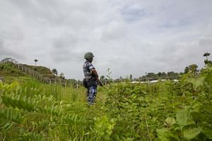 A Myanmar border guard police patrolling the fence in the