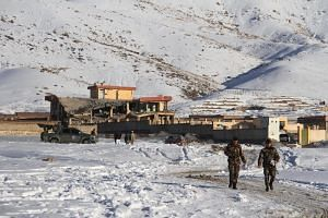 Afghan security forces walk near a site after a car bomb attack on a military base in the central province of Maidan Wardak on Jan 21, 2019.