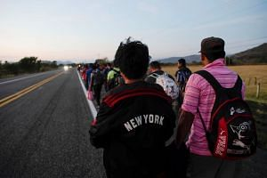 Migrants walk along a highway during their journey towards the United States, in Chauites, Mexico.