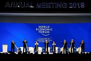 Musicians playing alphorns at the opening ceremony of the World Economic Forum in Davos yesterday. A PwC survey of nearly 1,400 CEOs found that 29 per cent believe global economic growth will decline over the next 12 months.