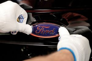 A worker attaches the Ford logo to a Fiesta car.