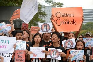 Activists holding placards rally against the lowering of the minimum age of criminal responsibility in front of the Senate building in Manila on Jan 25, 2019.
