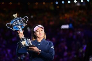 Japan's Naomi Osaka celebrates with the championship trophy during a presentation ceremony after her victory against Czech Republic's Petra Kvitova at the Australian Open, on Jan 26, 2019.