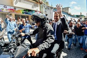 Venezuela's National Assembly head Juan Guaido (riding pillion on motorcycle) leaving after attending a gathering with opposition supporters at Bolivar Square in Chacao, eastern Caracas, on Friday.