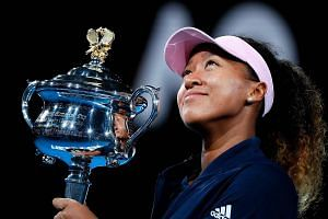 Japan's Naomi Osaka with the Daphne Akhurst Memorial Cup after her 7-6 (7-2), 5-7, 6-4 win over Petra Kvitova in the final which will see her become the first Asian singles world No. 1 tomorrow.
