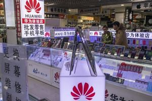 Customers browse a booth featuring Huawei products at a mall in Beijing, China, on Dec 17, 2018.