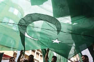 Pakistani men holding a national flag during an event in Lahore on Aug 12, 2018.