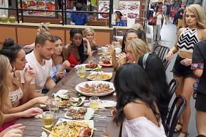 Video screengrab showing contestants of The Bachelor trying food in Singapore.