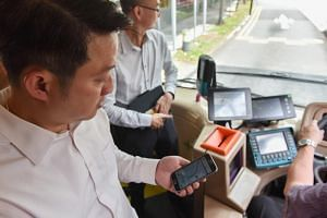 Senior Minister of State for Transport and Health Lam Pin Min testing the Mobility Assistance for the Visually Impaired and Special Users app on his smartphone.