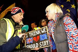 A pro-Brexit activist (left) and an anti-Brexit activist demonstrating outside the Houses of Parliament on Tuesday. Britain is legally on track to leave the European Union with or without a deal on March 29, unless it delays or stops the process.