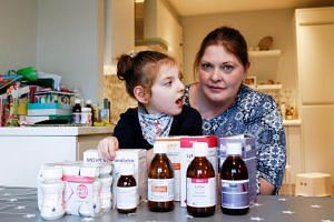Jo Elgarf with her daughter, Nora, and the latter's medicine at their home in London, Britain, on Jan 30, 2019. Nora has cerebral palsy and epilepsy and relies on imported medicine daily to stop her suffering seizures.