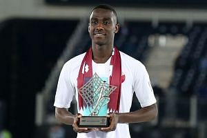 Qatar's Almoez Ali poses with the trophy for most valuable player of the tournament.