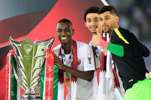 Qatar's Almoez Ali and team mates pose with the trophy as they celebrate winning the Asian Cup.