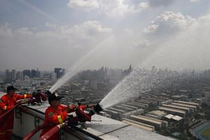 Thai officials spraying water from the top of a building in hopes of lowering the levels of harmful PM2.5 dust particles in Bangkok on Feb 1, 2019.