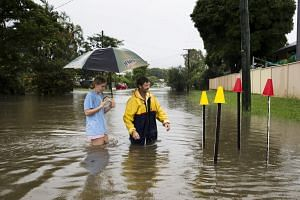 Resident Paul Shafer and his daughter Lily in flood waters near star pickets that show where the storm water cover has been removed in Hermit Park, Townsville, in northern Queensland on Feb 2, 2019.