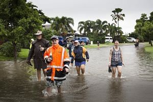 Floodwaters at Aplins Weir in Townsville on Friday. The local authorities issued a number of flood warnings yesterday morning. People wading in floodwaters in Townsville on Friday. Residents were told to leave their homes as Queensland's flood disast