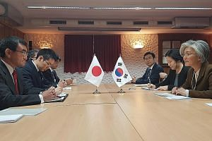 Japanese Foreign Minister Taro Kono (far left) meeting his South Korean counterpart Kang Kyung-wha (far right) on the sidelines of the World Economic Forum, in Davos, Switzerland, last month. The feud between both countries is beginning to damage eco