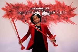 Neymar greeted his guests leaning on distinctive red crutches in keeping with the colour theme for the 'Nuit Rouge (Red Night)'.