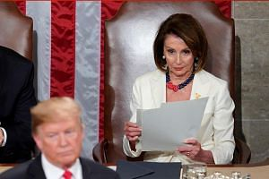 Nancy Pelosi (right) remains in her seat and looks through a copy of the speech as US President Donald Trump arrives to deliver his second State of the Union address on Feb 5, 2019.