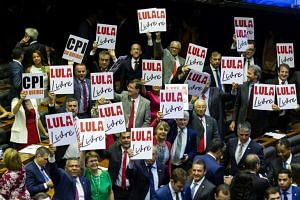 """Opposition deputies hold posters reading """"Free Lula"""" in support of Brazilian imprisoned former president Luiz Inacio Lula Da Silva, during the inauguration of the new legislature at the National Congress in Brasilia, on Feb 1, 2019."""