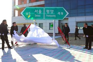 South and North Korean officials unveil a direction signboard during a ground-breaking ceremony to reconnect roads and railways across the divided Korean peninsula on Dec 26, 2018.