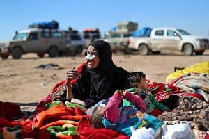 A woman and two children who had fled the fighting between the Syrian Democratic Forces (SDF) and ISIS militants in the Syrian village of Baghuz waiting to be screened and registered by the SDF on Sunday.