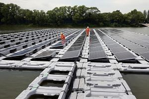A floating solar photovoltaic cell test-bed in Tengeh Reservoir in Tuas in 2016. While such panels cost more to install, they are up to 16 per cent more efficient because the water's cooling effect helps reduce thermal losses and extend their life, a