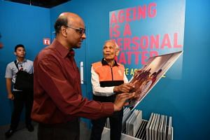 Science Centre Singapore senior tour guide John Siregar, 87, showing Deputy Prime Minister Tharman Shanmugaratnam a photograph of his students in his job as associate trainer in workplace literacy.