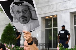 A protester holds a poster featuring Khashoggi during a rally over his disappearance in October 2018.