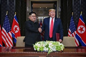 North Korean leader Kim Jong Un smiles as he shakes hands with US President Donald Trump during the signing of the declaration, after their first summit meeting in Singapore, Jun 12, 2018.