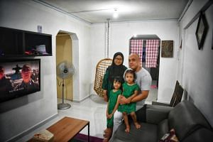 Mohammad Suhaimi Junaini with his wife and two daughters in their three-room flat in Jurong West.