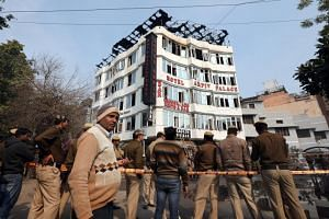 Locals and police on the scene at the hotel where a fire broke out in New Delhi, India, 12 February 2019.