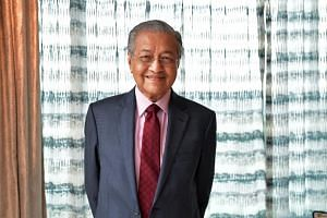 Malaysian Prime Minister Mahathir Mohamad, who is also Parti Pribumi Bersatu Malaysia chairman, handed over their new membership cards at a simple ceremony on Feb 12, 2019.