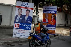 A man rides his motorcycle past political parties' electoral posters including that of Thai Raksa Chart Party (left) in Bangkok, Thailand, on Feb 11, 2019.