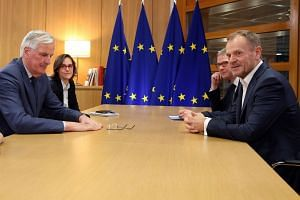 Michel Barnier (left) is welcomed by Donald Tusk before a meeting at the European Council in Brussels.