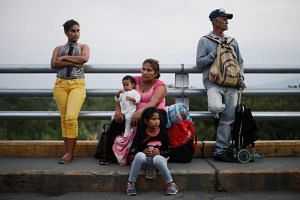 A Venezuelan family waits as they cross the Colombian-Venezuelan border on the outskirts of Cucuta, Colombia, on Feb 14, 2019.
