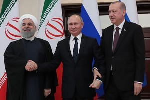(From left) Iranian President Hassan Rouhani, Russian President Vladimir Putin and Turkish President Recep Tayyip Erdogan pose for photographers during a trilateral meeting on Syria.