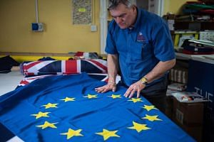 Andy Ormrod, the owner of Flying Colours Flagmakers Ltd, inspects a newly produced European Union flag in their premises in Knaresborough, northern England, on Feb 7, 2019.