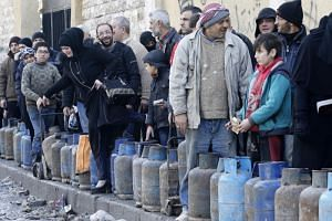 Syrians queue for gas canisters in the Salah al-Din district of the northern city of Aleppo on Feb 11, 2019.