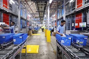 Pickers at FairPrice distribution centre retrieving ordered items from storage bins brought to them by AutoStore robots. FairPrice's training has helped workers quickly pick up new skills to make use of the new systems, and their work environment is