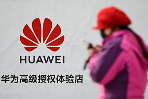 A woman using her smartphone walks past advertising outside a Huawei store in Beijing on Jan 29, 2019.