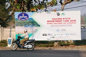 A rider passes by the Rakhine State Investment Fair 2019 bulletin board in Ngapali beach in Thandwe, Rakhine State, Myanmar on Feb 19, 2019.