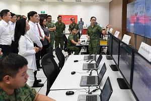 Senior Minister of State for Defence Heng Chee How (second from left) and members of the Advisory Council on Community Relations in Defence (Accord) watching a demonstration of cyber operators performing incident response in the Cyber Defence Test an