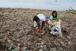 Women take part in an event to clear garbage from Lampung bay in the Sukaraja village, Bandar Lampung on Feb 21, 2019.
