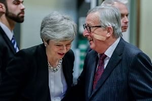 Theresa May (left) is welcomed by the EU's Jean-Claude Juncker ahead of a Brexit meeting in Brussels.