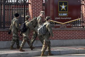 US soldiers walking past a gate of the US Camp Humphreys in Pyeongtaek, on Feb 21, 2019.