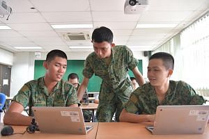 Private Clement Chin (left) presenting his work to Cyber Defence School trainer Fuji Neo (standing) in December. Pte Chin is in the pioneer cohort of NSF cyber specialists.