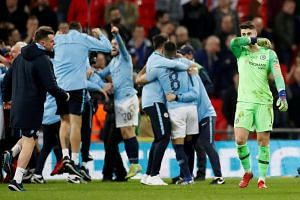 Chelsea's Kepa Arrizabalaga (right) looks dejected as Manchester City players and staff celebrate winning the final at the Wembley Stadium, London, Britain, on Feb 24, 2019.
