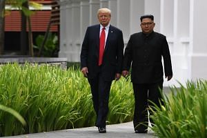 North Korea's leader Kim Jong Un (right) walks with US President Donald Trump during their historic summit in Singapore, on June 12, 2018.